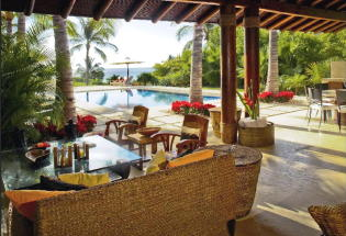 Outdoor seating area with view of pool and Bay.