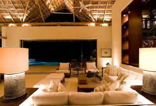Nightime view of large comfortable seating area under Palapa.