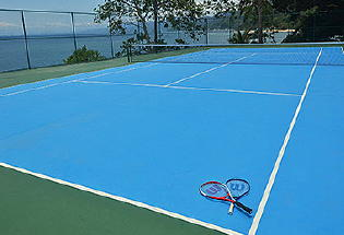 Tennis court with view of ocean.