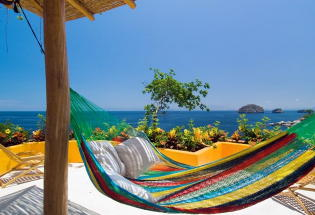 Relax in hammock looking out over bay and Los Arcos Islands.
